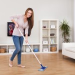 Portrait Of Young Woman Mopping Floor At Home